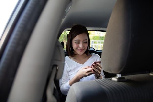 Азиатская женщина-подросток, использующая смартфон на заднем сиденье автомобиля, пассажиры используют приложение, чтобы заказать поездку, и концепция совместного использования одноранговой поездки.