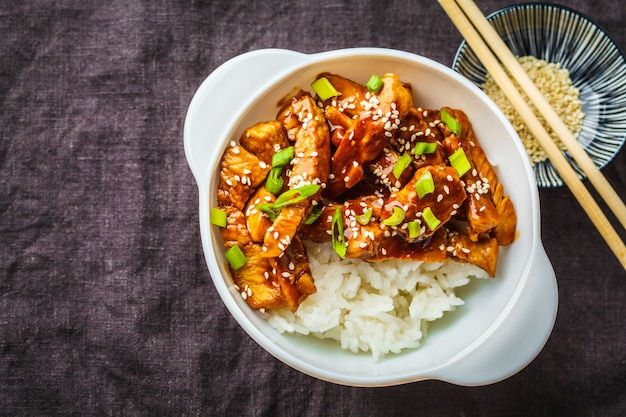 Asian teriyaki chicken with rice, sesame and green onions in white bowl.