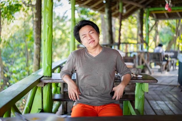 아시아계 태국인 중국인은 주말에 녹색 빈티지 파빌리온의 자연 환경에서 이 휴가날에 미소를 짓고 휴식을 취합니다.