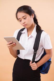 アジアのタイの大学生女性。バックパックとコンピューターのタブレットを運ぶ深刻な重点を置かれた大学生の教育の肖像画
