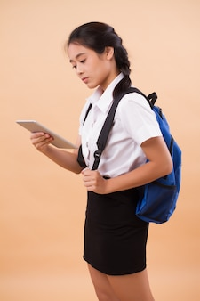 Asian thai college woman student. education portrait of serious, stressed university woman student carrying backpack and computer tablet