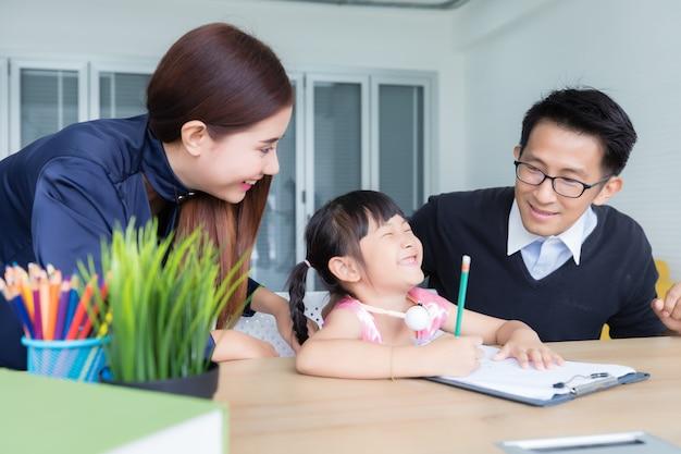 アジアのタイ人の両親が笑顔で幸せな顔で娘たちを教えています。自宅で勉強するというコンセプトで