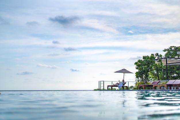 아시아 태국 십 대 여성 흰 드레스는 태국 남동부 뒤에 바다 해변과 인피니티 풀 옆에 나무 침대에서 이완합니다.