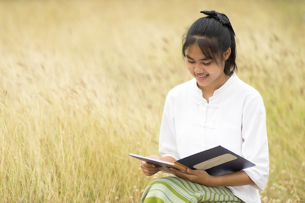 Asian thai woman sitting and reading a book at meadow field.