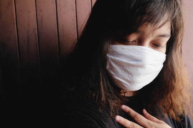 Asian thai woman wearing a white cloth mask for prevent the covid-19 or corona virus and air pollution value pm 2.5 in thailand. she is suffocating in respiratory system. health and illness concept