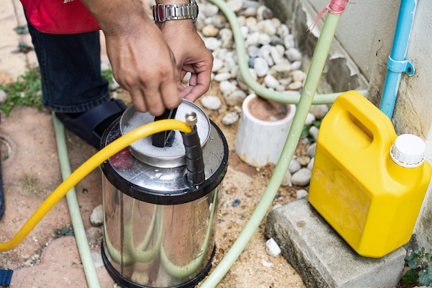 Asian thailand termite staff company is spraying the destroy chemical liquid in to white ant nest in the wood around human house.