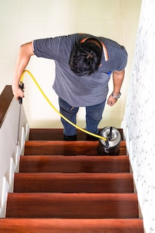 アジアのタイのシロアリスタッフ会社は、人間の家の周りの森の白い蟻の巣に破壊化学液を噴霧しています。