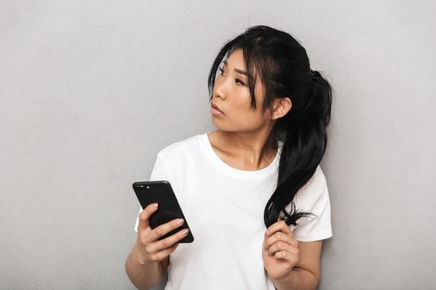 携帯電話を使用して灰色の壁に孤立したポーズをとってアジアの思考美しい若い女性。