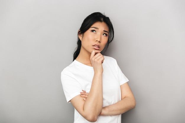 灰色の壁に孤立したポーズをとってアジアの思考美しい若い女性。