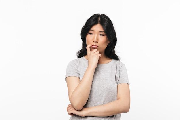 アジアの思考美しい若い女性が白い壁に孤立してポーズをとる。