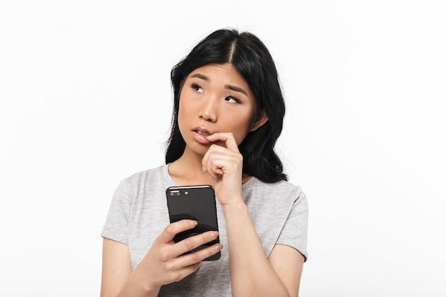 携帯電話を使用して白い壁に隔離されたポーズをとるアジアの思慮深い美しい若い女性。