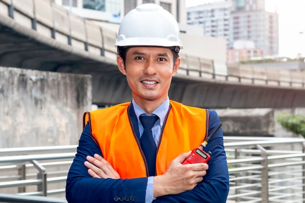 Asian thoughtful engineer smiling with arms crossed.