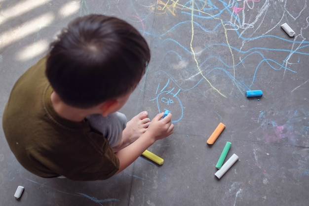 Asian toddler boy child drawing with colored chalk on asphalt sidewalk outdoors, little young kid playing alone