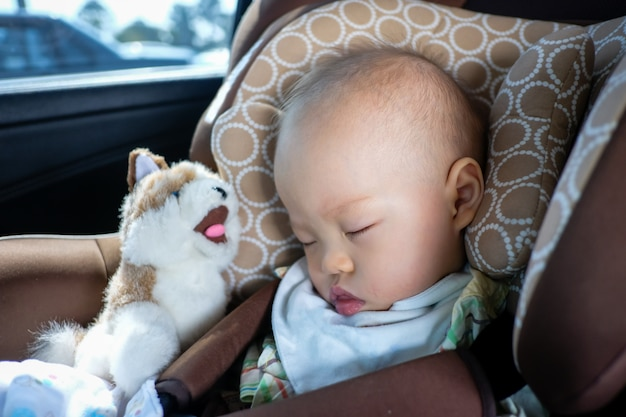 Asian toddler boy child sleeping in car seat. child traveling safety on the road. safe way to travel fastened seat belts in vehicle with young kid concept