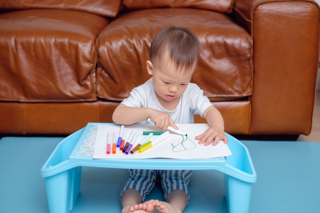 Asian toddler boy drawing, scribbling with colorful maker