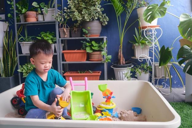 家で砂だけで遊んでアジア幼児男の子、おもちゃの建設機械で遊ぶ子供