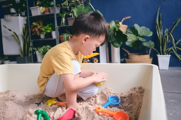 家で砂だけで遊んでいるアジアの幼児男の子、都市の家の庭で砂のおもちゃで遊んでいる子供