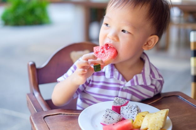 Asian  toddler boy sitting in high chair using hands eating watermelon, pineapple, dragon fruit