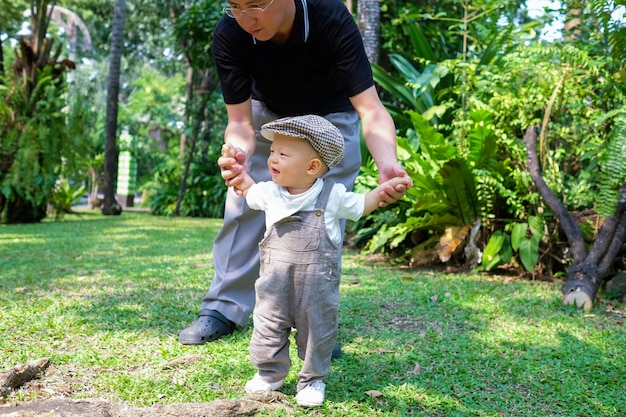 Asian toddler boy walking with his father