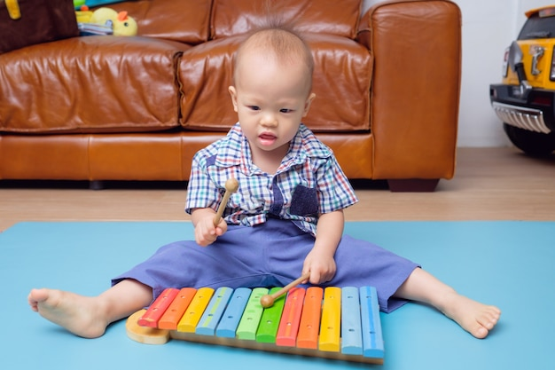 Asian toddler plays a wooden toy xylophone