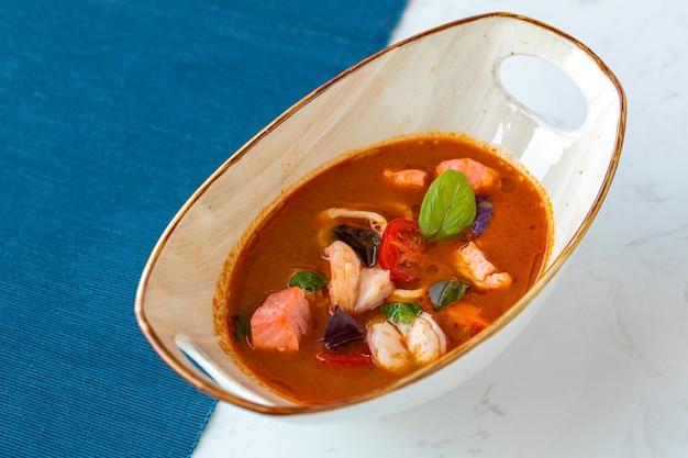 灰色のテーブルのボウルにアジアのトムヤムクンのスープ