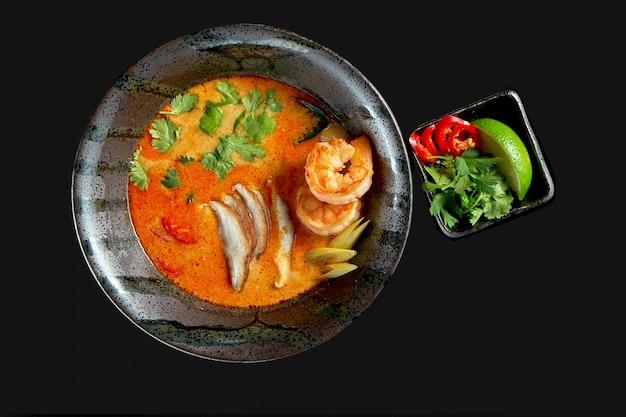 Азиатский суп том ям с креветками, грибами шиитаке, осьминогами, помидорами и рисом в тарелке. классическая азиатская кухня. доставка еды. изолированные на черном