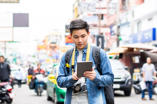 Asian tourist backpacker using tablet while traveling  in khao san road thailand
