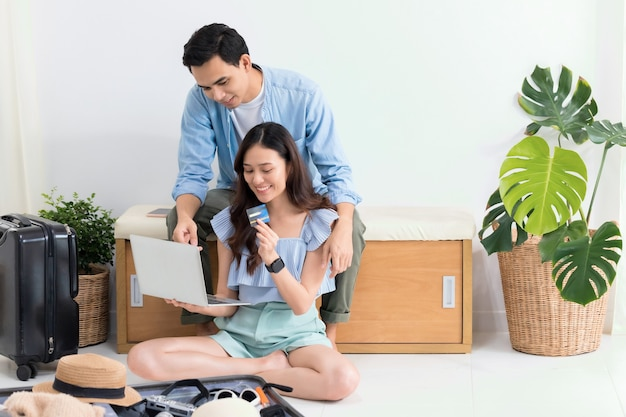 Asian tourist couple planning travel information with laptop and packing suitcases for travel before travel date at home background.