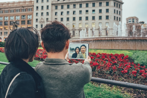 Asian tourist couple taking a selfie on the tablet
