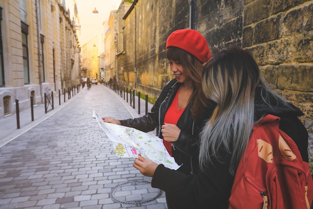 Asian tourist looking on map searching for direction in bordeaux, france