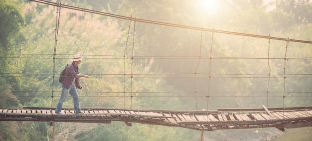 Азиатский туристический человек, идущий по старому и сломанному деревянному мосту
