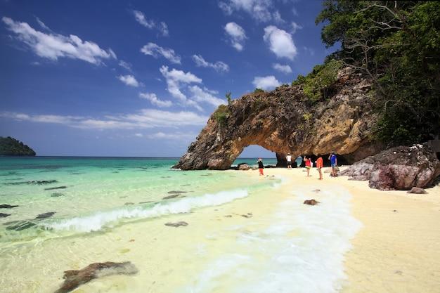 Азиатские туристы посещают природную каменную арку на острове ко кхай