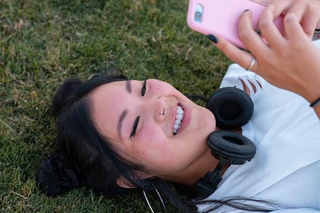 Азиатский турист фотографирует на мобильный в парке