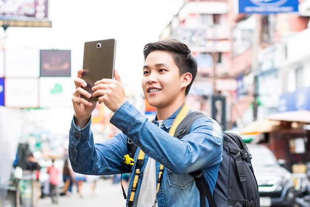 Asian tourist taking photo with tablet computer while traveling in bangkok, thailand