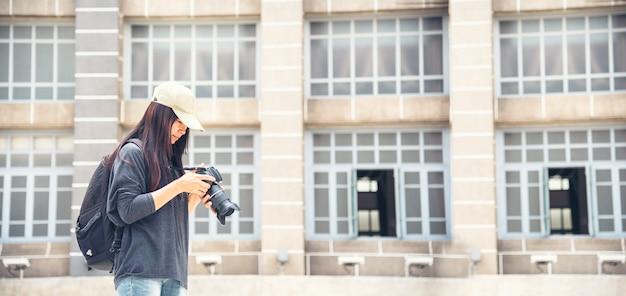 전문 카메라를 사용하는 아시아 관광객. 오래 된 마에서 배낭과 사진 카메라와 함께 여성 젊은 여행자.