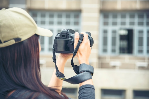 Азиатский турист с профессиональной камерой. женский молодой путешественник с рюкзаком и фотоаппаратом в старом городе.