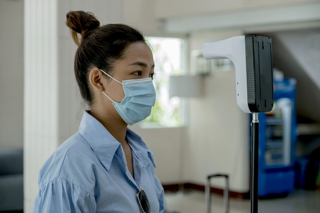 Asian tourist woman has checked body temperature with thermal temperature scanner detector travel.