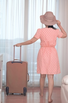 Asian tourist woman in a pink dress standing with her luggage in the hotel bedroom, happy women lifestyle with holiday summer travel vacation concept