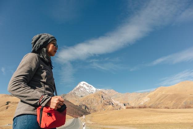 冒険の概念で山の中の道を歩いてアジア観光客の女性。