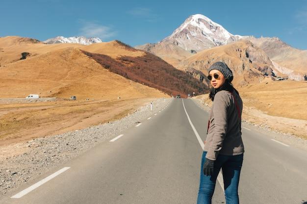 冒険の概念で山の中の道を歩くアジアの観光女性。
