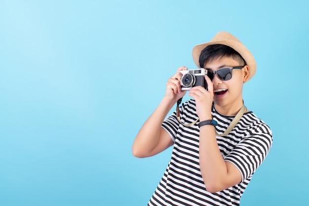 アジアの観光客は青色の背景で写真を撮ることを楽しんでいます。孤立した
