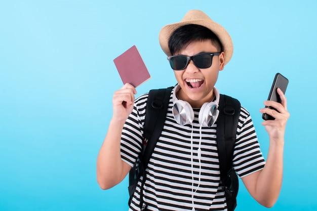 アジアの観光客は青で止め金とスマートフォンを保持します