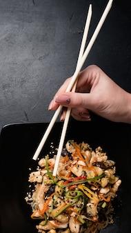 Азиатская традиционная культура питания. женщина ест салат из куриных грибов и овощей с палочками.