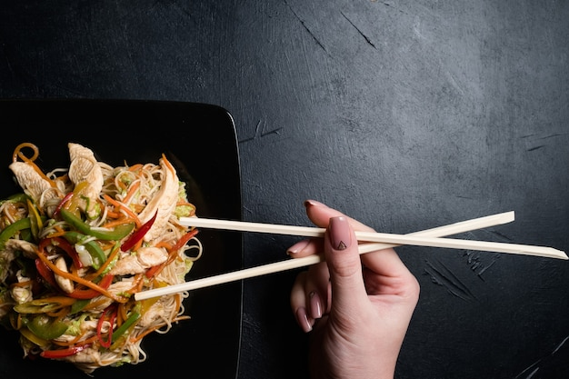 Азиатская традиционная культура питания. женщина ест куриный овощной салат с палочками для еды