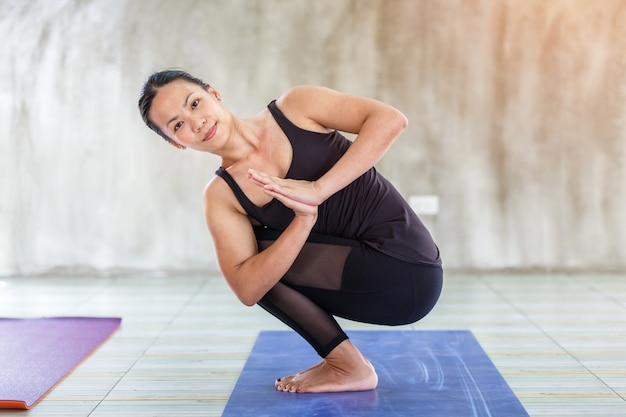 Asian trainee strong woman practicing difficult yoga pose