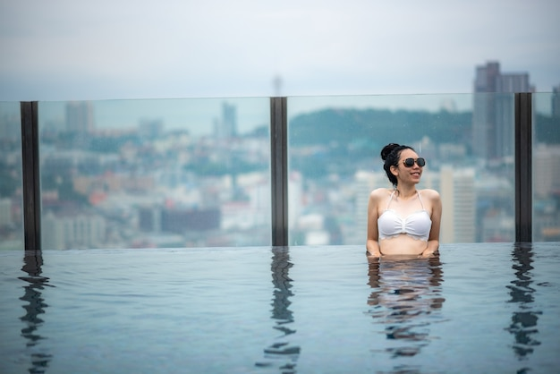 アジア旅行のコンセプト。ホテルの屋上プールから街の空の景色を楽しんでいる若い女性、休暇中に屋外の美しい女の子のライフスタイル