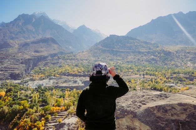 Азиатский путешественник, глядя на горный хребет пейзаж осенью