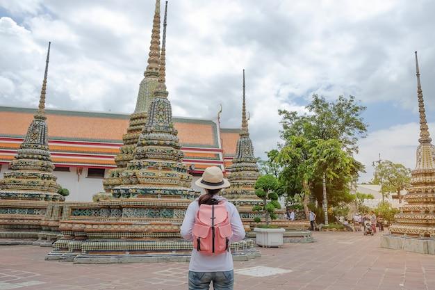 Asian traveler looking to pagoda at wat pho, bangkok, thailand
