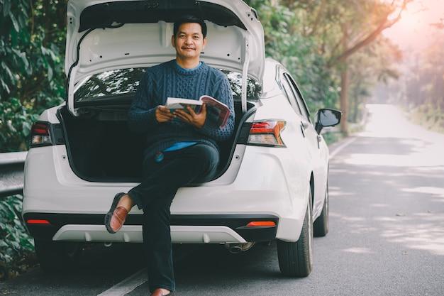 Азиатский путешественник сидит и читает книгу с открытым багажником автомобиля