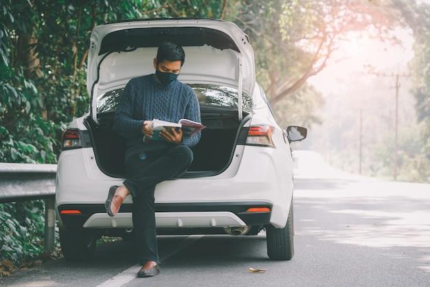 Азиатский путешественник в маске и читает книгу с открытым багажником автомобиля